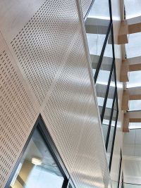 Perforated acoustic wall panels in white pigmented oak veneer