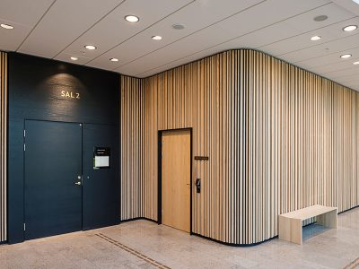 The walls in the public space are cladded with timber slat modules