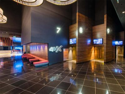 Walnut panels are cladding screen entrances at Al-kout cinema