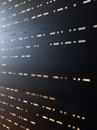 Black stained wooden veneer with glass perforation