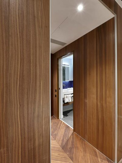 Hotel room at RAF Club cladded in walnut plank panels