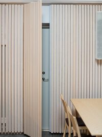 Wood cladding panels hiding the door to the ventilation