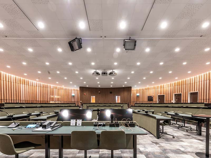 Auditorium cladded with slatted timber panels in walnut