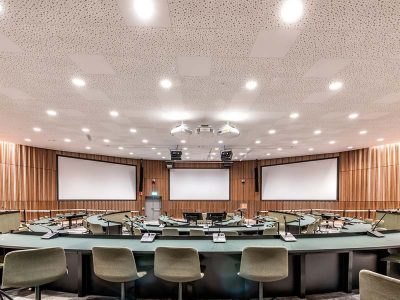 Lecture hall cladded with wooden panels in walnut