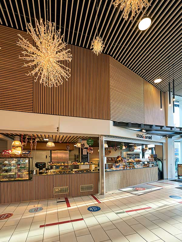 Coffee shop clad in slatted wood panels