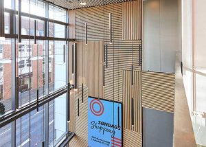 Entrance wall with a creative wood-clad installation