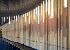 Wall designed in sound waves of slatted wood panels
