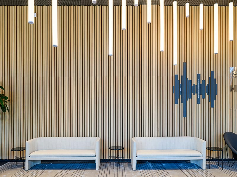 Office lobby with back drop wall designed with oak veneered wood slats